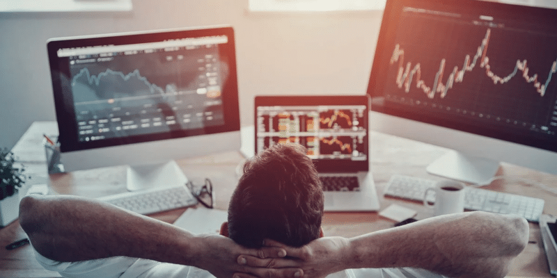 resting man in front of two screens