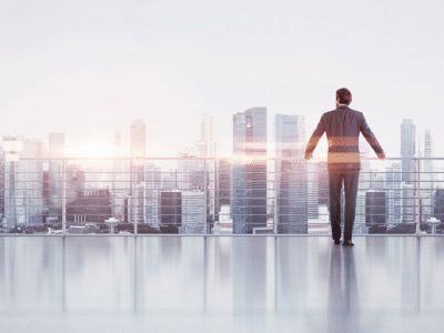 businessman looks at the big city from the balcony